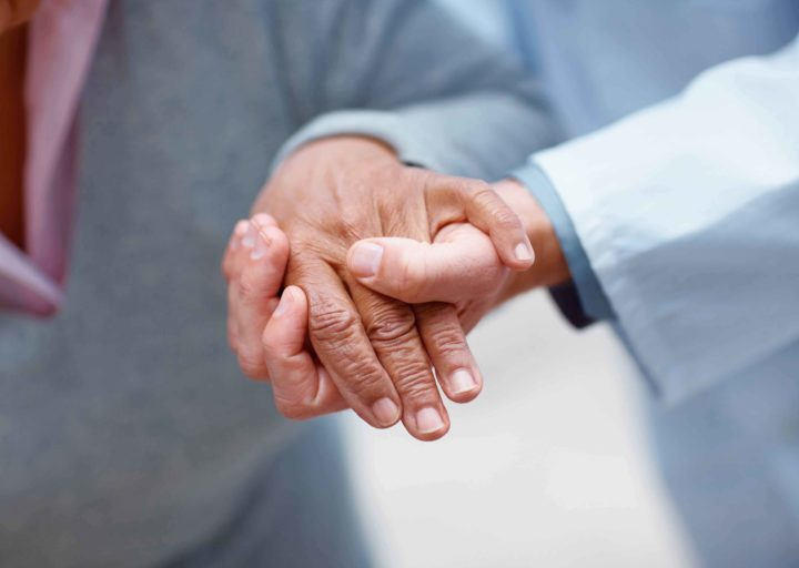 Closeup of an elderly woman's hand being held by a doctor , focus on hands